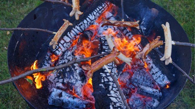 Würstchen über einer Feuerschale grillen
