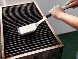 Grillrost wird mit Bürste gereinigt